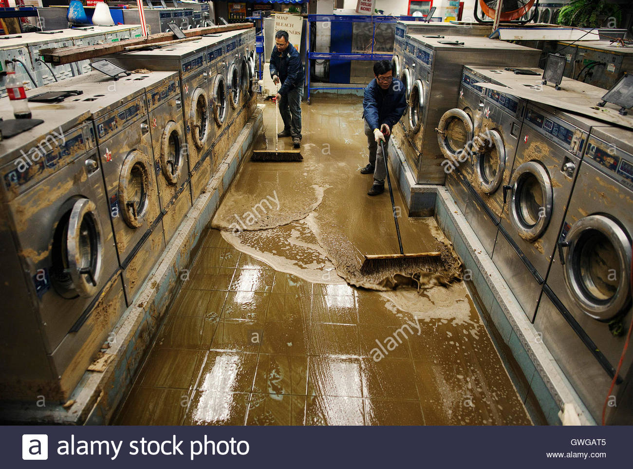 eddie-liu-r-uses-a-broom-to-clean-up-mud-and-water-from-extensive-gwgat5